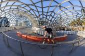 View of cyclist riding along the Webb Bridge in Docklands, Melbourne — Stock Photo
