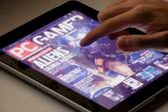 Reading magazine using a tablet — Stockfoto
