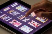 Reading magazine using a tablet — Stock Photo