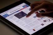 Reading online newspaper on ipad — Stock Photo