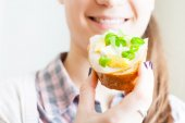 Woman eating sandwich with cheese and green vegetables onion — Stock Photo