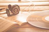 Headphones on music scores vinyl record music background — Stock Photo