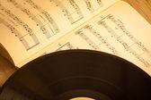 Vinyl record on music scores music background — Stock Photo