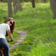 Young woman cyclist in the forest park recreation — Stock Photo #70310783