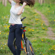 Young woman cyclist in the forest park recreation — Stock Photo #70311689