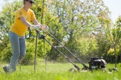Young female in yard - pushing grass trimming lawnmower — Stock Photo