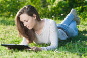 Young woman using computer tablet pc outdoor in the park — ストック写真