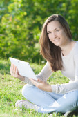 Young woman using computer tablet pc outdoor in the park — Stock Photo