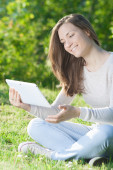 Young woman using computer tablet pc outdoor in the park — Foto de Stock