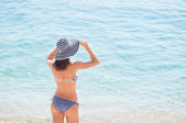 Young woman at the beach holding hat — Stock Photo