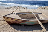 Wooden empty boat with two oars on beach — Stock Photo