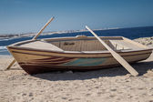 Wooden boat with two oars on beach — Stock Photo