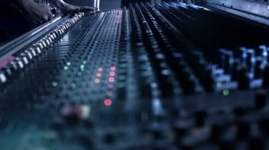 Audio Engineer adjusting knobs and faders on his mixing console desk during a live event. — Stock Video