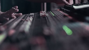 Audio Engineer adjusting faders on his mixing console desk during a live event. — Stock Video