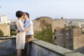 Newlyweds kissing at the rooftop — Stock Photo