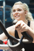 Young girl riding stationary bike — Stock Photo