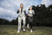 Attractive young couple running in the park — Stock Photo