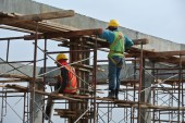 Construction workers dismantling beam formwork — Stock Photo