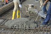 Construction Workers casting concrete using concrete hose — Stock Photo