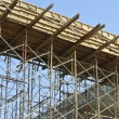 Timber beam formwork supported by row of scaffolding — Stock Photo #64349907