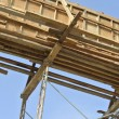 Timber beam formwork supported by row of scaffolding — Stock Photo #64349923