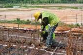 Construction workers fabricating beam reinforcement bar at construction site — Stock Photo