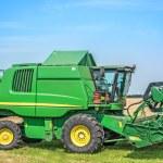 Harvester. Combine harvester harvesting wheat on sunny summer. — Stock Photo #77897864