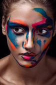 Close up portrait of a young woman with unusual makeup on a dark black background — Stock fotografie