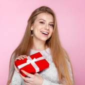 Joyful girl in white sweater with a red gift box on the pink background, Valentines Day, holidays, happiness, International Women's Day — Стоковое фото