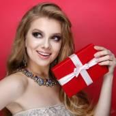 Elegant blonde woman holding small gift box with ribbon. Studio portrait over red background. Happy birthday. Valentines Day. Joyful — Stock Photo