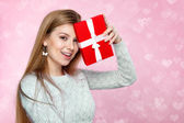 Valentines Day. Sweet blonde woman holding a gift box. heartshaped bokeh background Joyful — Stockfoto