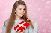 Valentines Day. Sweet blonde woman holding a gift box. heartshaped bokeh background Joyful — Foto de Stock