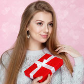 Valentines Day. Sweet blonde woman holding a gift box. heartshaped bokeh background Joyful — Stock Photo