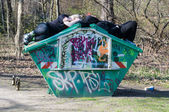Two young adults sleeping on a dumpster — Stock Photo