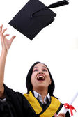 Happy young female graduate tossing up her hat — Stock Photo