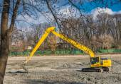 Yellow excavator doing maintenance work on the city park. No trespassing — Stock Photo