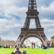 Young woman laying on the gras in front of Eiffel tower — Stock Photo #79744332