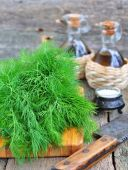 Bunch of fresh dill with olive oil on a wooden table — Stock Photo