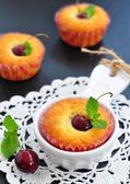 Cakes with sweet cherry and cup milk on a black background — Stock Photo