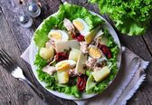 Salad of lettuce, iceberg lettuce, with canned tuna, dried tomatoes, boiled potatoes, capers and parmesan cheese, dressed with olive oil. Selective focus. rustic style. — Stock Photo