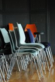 Groups of metal chairs are stacked in room — Stock Photo