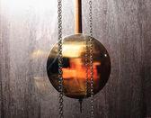 Metal pendulum clock swinging in wood background — Stockfoto