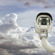 Front view of surveillance camera against clouded sky background — Stock Photo #65018621