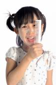 Smiling asian little girl with applying make up baby powder on f — Стоковое фото