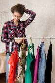 Girl chooses dresses  — Stock Photo