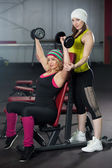 Two female partners train in gym with dumbbells — Stock Photo