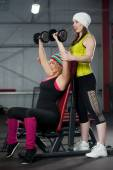 Coach assists to female in training with dumbbells in gym — Stock Photo