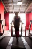 Sporty girl walks on treadmill — Стоковое фото