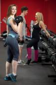 Smiling girl lifts weights in fitness center, with friends on th — Stock Photo