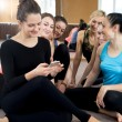 Постер, плакат: Group of happy sporty women using mobile phone on break in sport